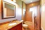 Guest bath featuring wood cabinetry and granite tops