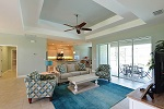 Great room features a tray ceiling and pocket sliders to lanai