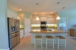 Kitchen with gathering island and designer pendant lights