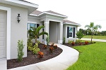 Front entry with sweeping sidewalk and Florida friendly landscaping